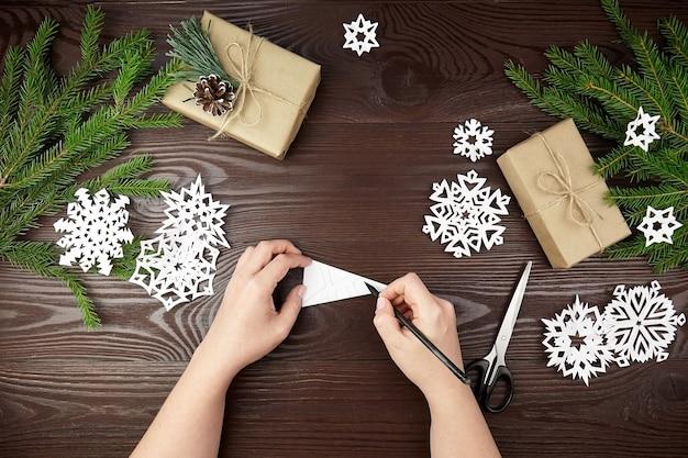 Mani che fanno i fiocchi di neve di carta bianca sulla tavola di legno