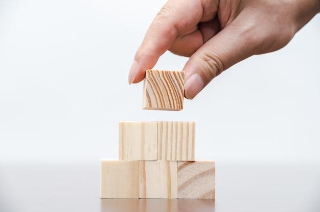 Le mani di un uomo d'affari che sta impilando blocchi di legno. concetto di affari.