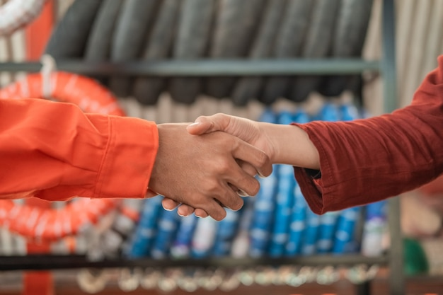 Le mani del meccanico maschio in un'uniforme wearpack stringono la mano a un cliente di sesso femminile contro un porta pneumatici