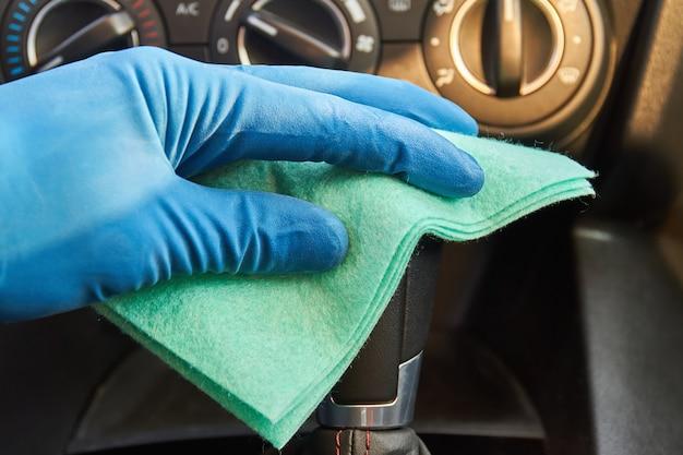 Le mani dell'uomo in guanti protettivi blu stanno pulendo la leva del cambio con un panno