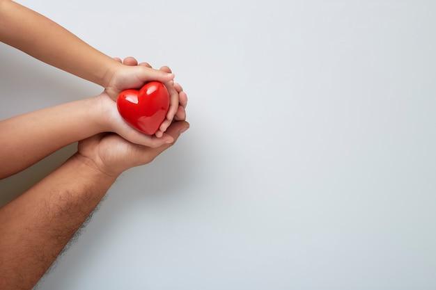 Mani dell'uomo e del bambino con un cuore rosso sul muro bianco