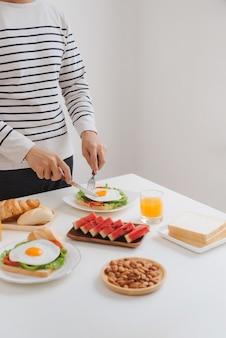 Le mani dell'uomo tagliano le uova su carta, servite con pane, erbe aromatiche, salsiccia e succo fresco.