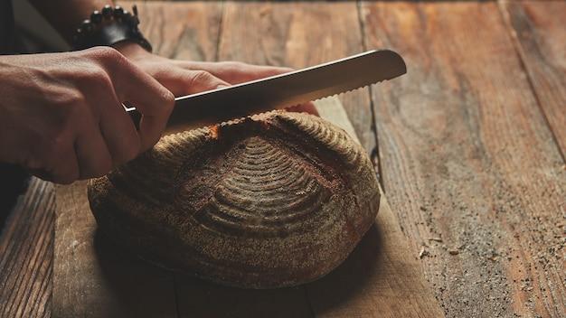 Mani di un uomo che taglia pane di segale fresco su uno sfondo di legno