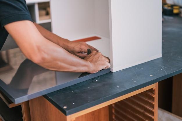 Mani di un uomo che fissa una cerniera su una superficie per una cucina
