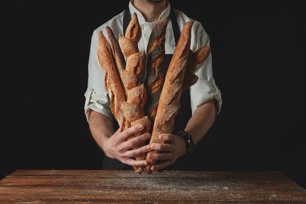 Uomo di mani che tiene le baguette su un tavolo di legno