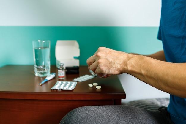Uomo di mani in possesso di pillola e bicchiere d'acqua sul tavolo mentre era seduto sul divano e andando a prendere la medicina