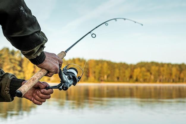 Le mani di un uomo in un piano urp tengono in mano una canna da pesca, un pescatore pesca i pesci all'alba vacanza di hobby di pesca