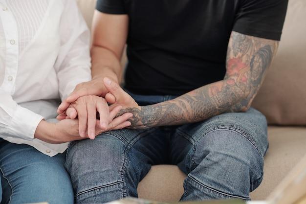 Mani dell'uomo con le braccia tatuate che tengono le mani di sua madre matura per rassicurarla e sostenerla