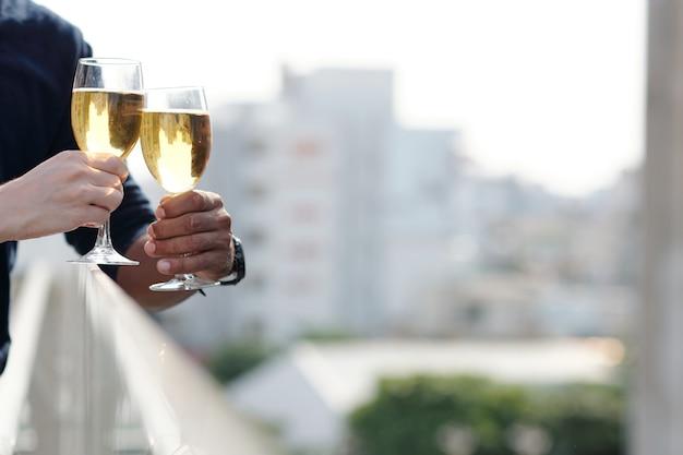 Mani di uomo e donna che tintinnano bicchieri di vino bianco freddo quando si trovano sul balcone, una grande città sullo sfondo