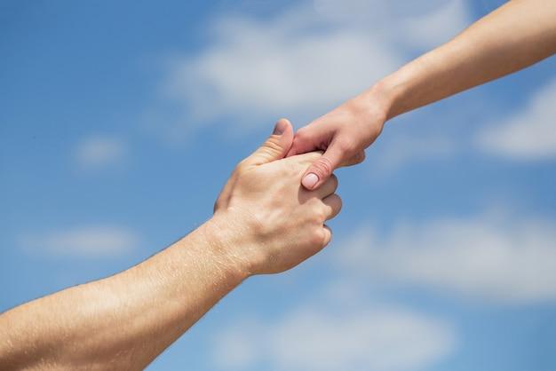 Mani dell'uomo e della donna che si raggiungono l'un l'altro, supporto. solidarietà, compassione e carità, salvataggio. dare una mano. mani di un uomo e di una donna su sfondo blu cielo. dare una mano.