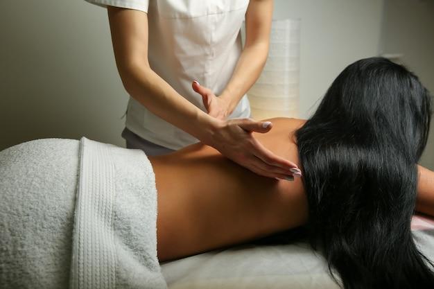 Mani di un massaggiatore che fa massaggio di una donna
