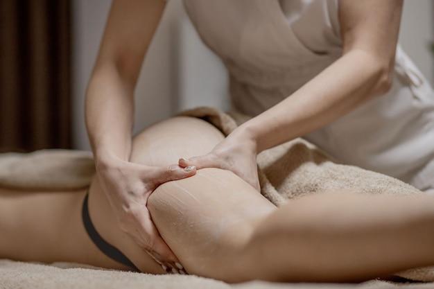 Le mani del massaggiatore nel salone della stazione termale fanno il massaggio a una giovane donna.