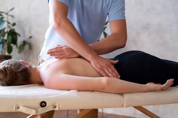 Mani che massaggiano la schiena da vicino