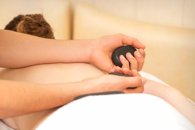 Le mani del massaggiatore tengono pietre calde nere che massaggiano la schiena di una giovane donna adulta nel salone della stazione termale