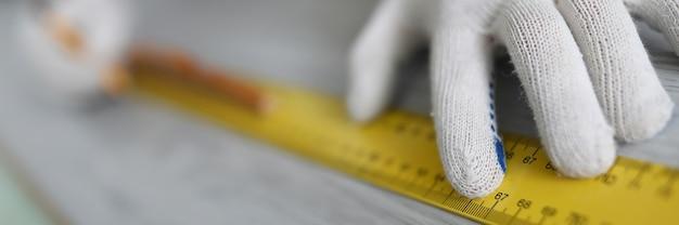 Mani del maestro che effettuano misurazioni con righello su laminato