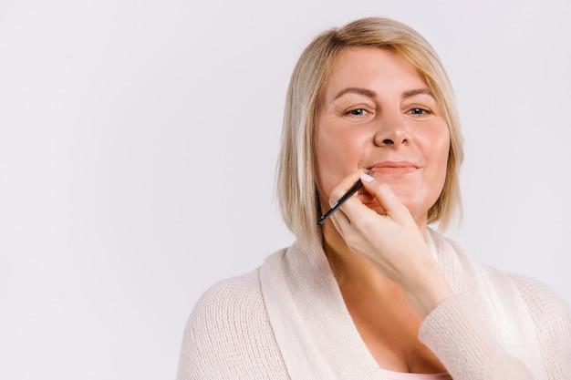 Le mani del maestro delineano le labbra con una matita per una donna adulta. concetto di bellezza e trucco su priorità bassa bianca. foto di alta qualità