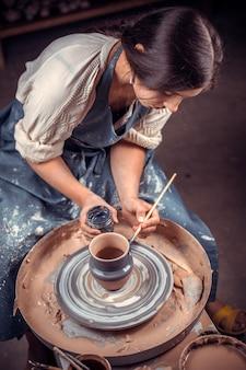 Mani del maestro vasaio e vaso di argilla sul primo piano del tornio del vasaio