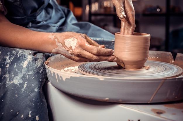 Mani del maestro vasaio e vaso di argilla sul primo piano del tornio da vasaio