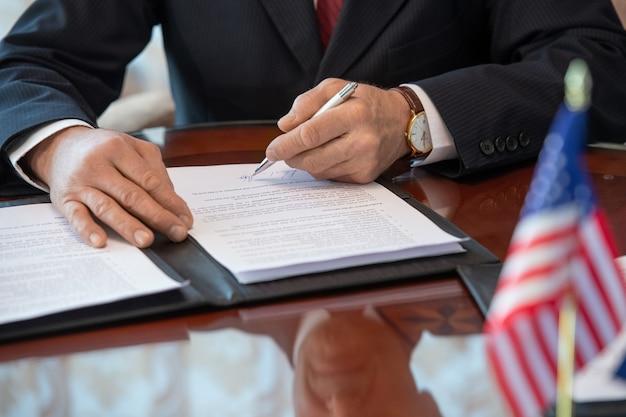 Mani del delegato americano maturo in abiti da cerimonia che firmano un contratto di partnership commerciale e puntano alla firma mentre sono seduti al tavolo
