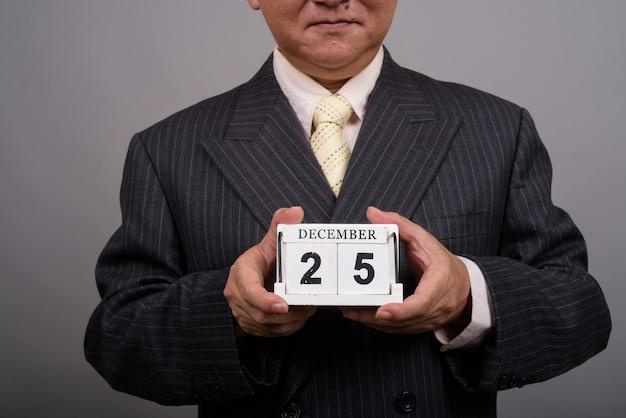 Le mani dell'uomo d'affari asiatico maturo che tengono i blocchi del calendario contro