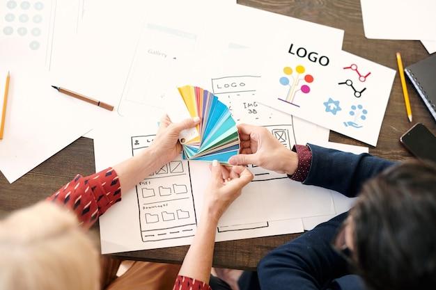 Mani di designer donna matura con tavolozza che si consultano con un collega maschio su quale colore scegliere per il loro nuovo progetto