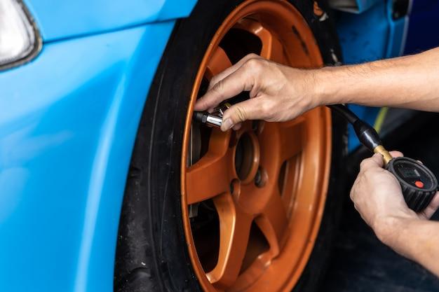 Mani dell'uomo meccanico che controllano la pressione dell'aria della gomma