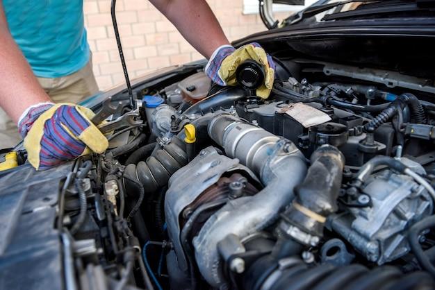 Le mani dei meccanici in guanti protettivi con il motore dell'auto si chiudono