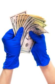Mani in guanti medici che tengono un pacco di dollari.