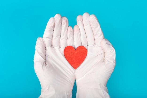 Mani in guanti medici che tengono un modello rosso di forma del cuore su fondo blu. cardiologia. donazione di organi o concetto di cuore sano