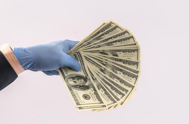 Mani in guanti medici che tengono pila di dollari per sicurezza, epidemia di denaro sporco. tutto per la salute