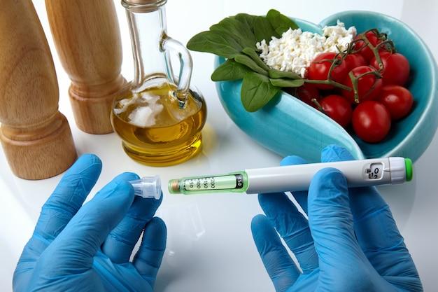 Le mani in guanti medicali posizionano un ago su una penna a siringa con insulina sullo sfondo di una ciotola di cibo. concetto di calcolo della dose di insulina