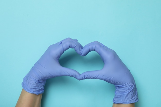 Le mani in guanti medicali mostra il cuore su sfondo blu isolato