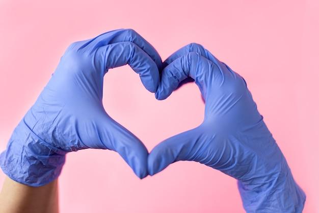 Le mani in guanti medici mostrano un cuore