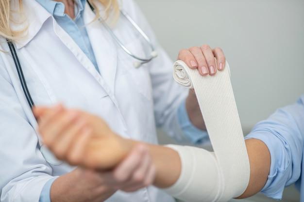 Le mani dell'operatore sanitario stanno bendando in modo affidabile con la fasciatura elastica dell'avambraccio ferito del paziente, nessun volto è visibile