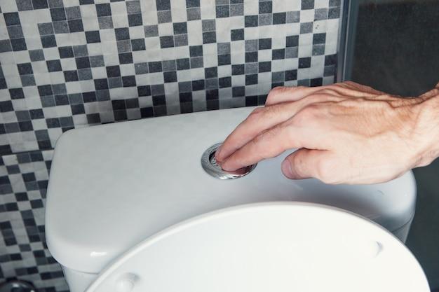 Mani di uomini, premere il pulsante dell'acqua, tirare lo sciacquone, il concetto di salute.