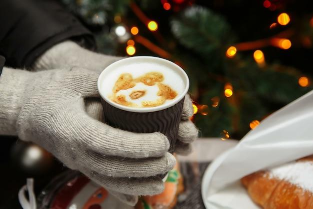 Le mani in guanti tengono una tazza di caffè calda. caffè da portare in inverno.
