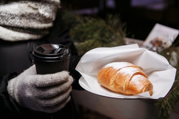 Le mani nei guanti tengono una tazza di caffè calda e un croissant. caffè da portare in inverno.