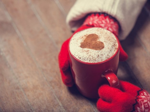 Mani in guanti che tengono tazza di caffè calda