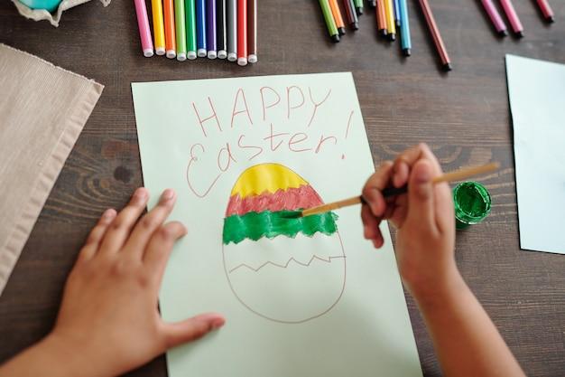 Le mani della bambina di razza mista che dipingono un grande uovo di pasqua su carta bianca tra evidenziatori colorati e pastelli mentre sono seduti da un tavolo di legno