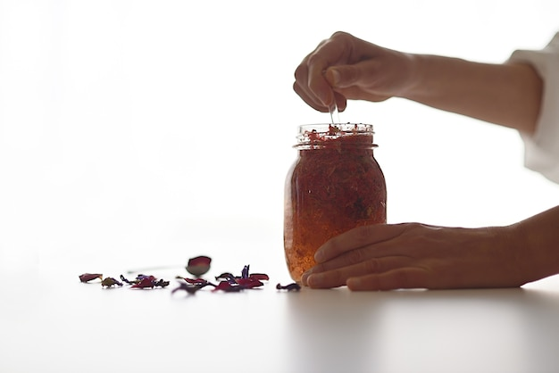 Mani che mescolano fiori e oli essenziali in una bottiglia di vetro, rendendo cosmetici naturali in un laboratorio.
