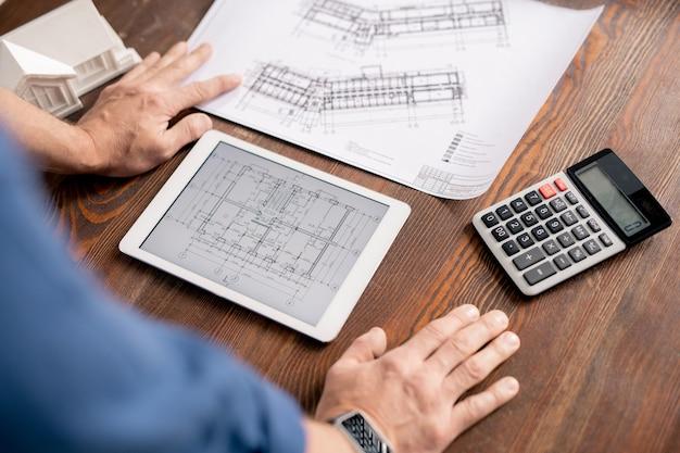 Mani dell'ingegnere moderno che si appoggia sul tavolo di legno mentre si piega su tablet con schizzo elettronico
