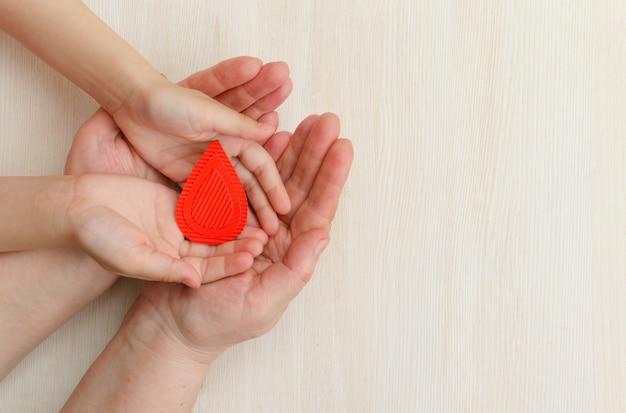 Le mani della madre e del bambino tengono una goccia di sangueconcetto di donare il sangue per la giornata mondiale dell'emofilia