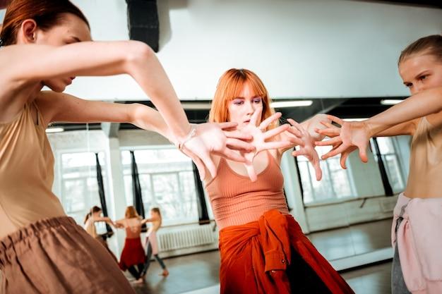 Le mani si muovono. bella insegnante di danza con i capelli rossi che sembra seria mentre spiega le mosse ai suoi studenti