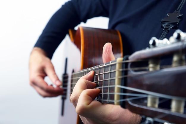 Mani del musicista che gioca sulla chitarra classica