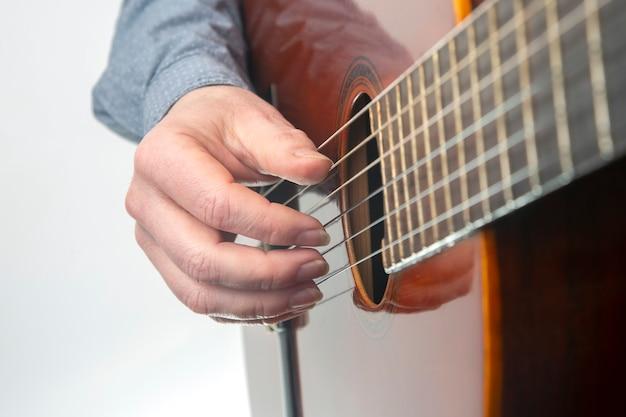 Mani del musicista che suona la chitarra classica