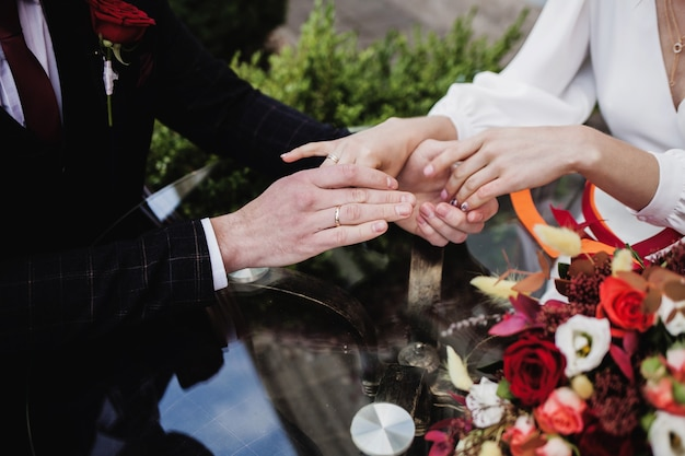 Le mani degli sposi con le fedi nuziali. il bouquet della sposa è sul tavolo