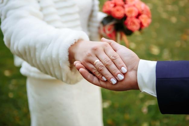 Mani o mani di sposi con fedi nuziali e bouquet da sposa