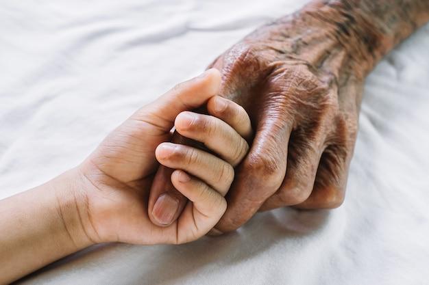 Le mani del vecchio e la mano di un bambino sul letto bianco