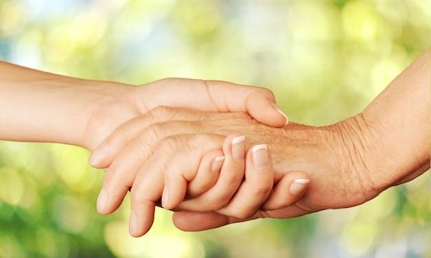 Mani del vecchio e di una giovane donna. avvicinamento.