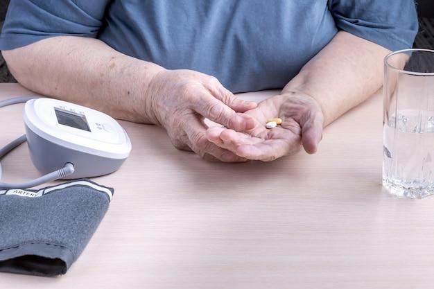 Le mani di una donna anziana con pillole un misuratore di pressione sanguigna e un bicchiere d'acqua